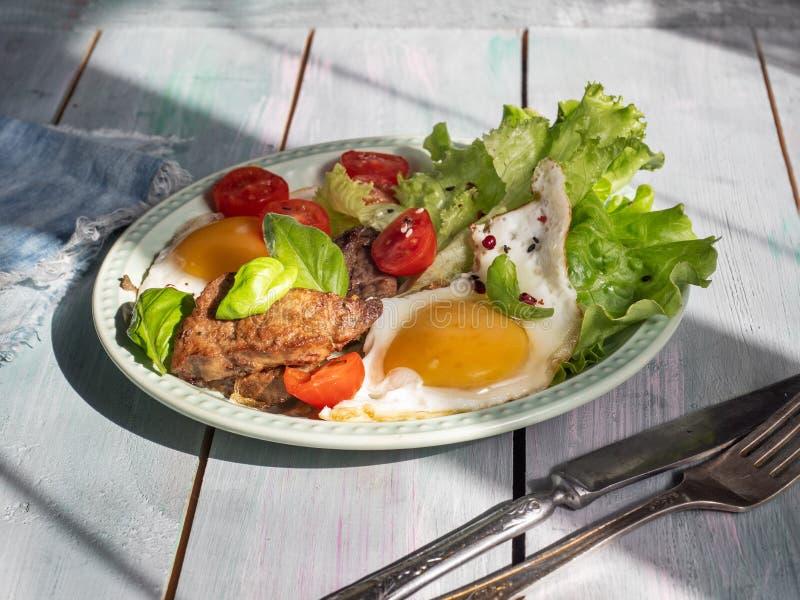 Een hartelijke lunch van gebraden eieren met gebraden lever en kersentomaat, bladsla Dien op een rustiek dienblad in een rustieke royalty-vrije stock fotografie