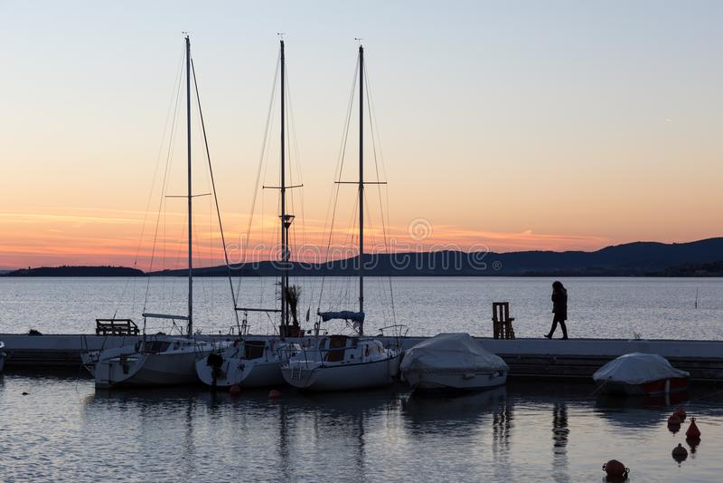 Een haven op een meer bij zonsondergang, met diverse boten en een vrouw t stock afbeelding