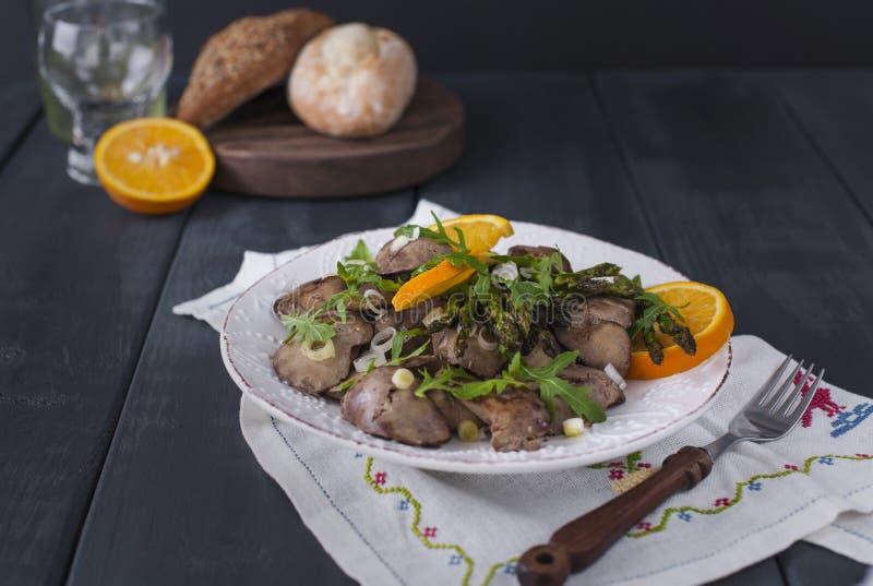 Een heerlijk gezond diner, een warme salade van de kippenlever met sinaasappelen en rucola, op een zwarte houten achtergrond Vrij stock foto's