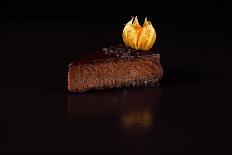 Een heerlijke chocoladekaastaart op een zwart zijaanzicht als achtergrond stock afbeelding
