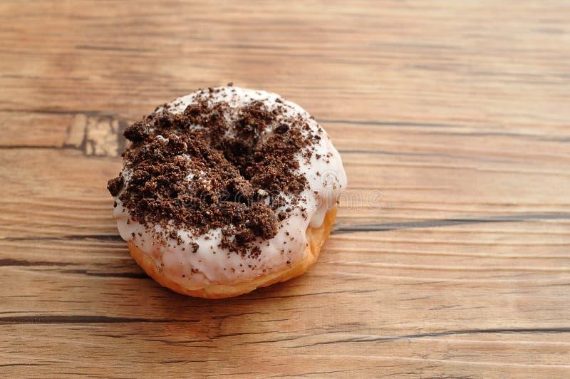 Een heerlijke die doughnut in chocoladesproeiers wordt behandeld stock foto's