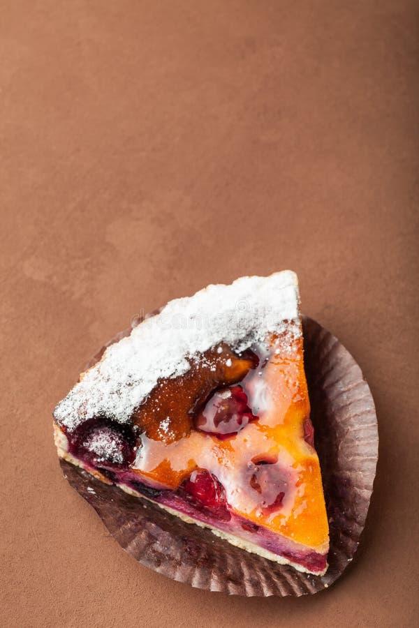 Een heerlijke eigengemaakte pastei met pruimen wordt bestrooid met suikerpoeder op een document servet stock foto's