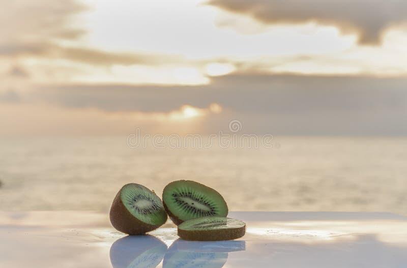 Een heerlijke gesneden groene kiwi met de zonsondergang op de achtergrond - Harige groene kiwi - plaatst uit elkaar om tekst te s stock foto