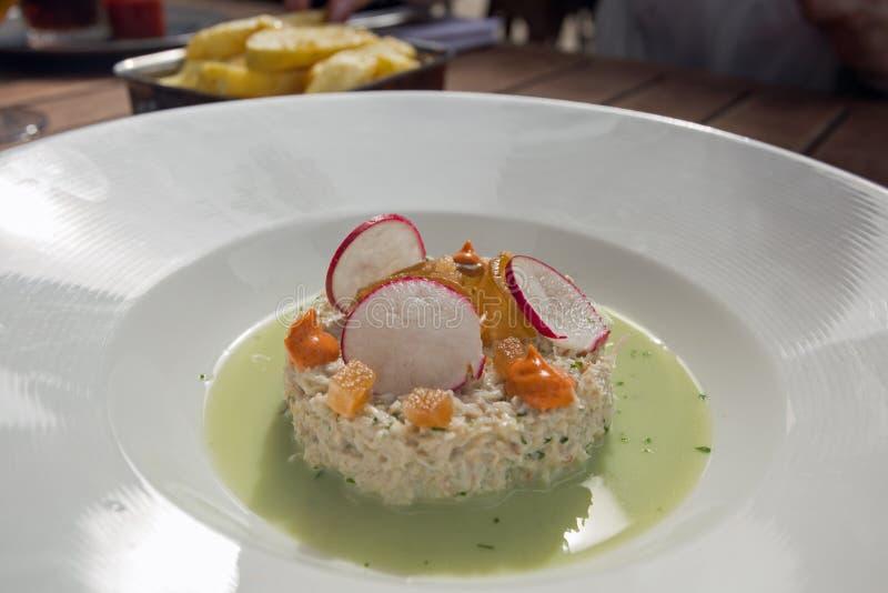 Een heerlijke krabsalade met witte waterkers en Paprikasausen en een bovenste laagje van peer en radijs stock afbeelding