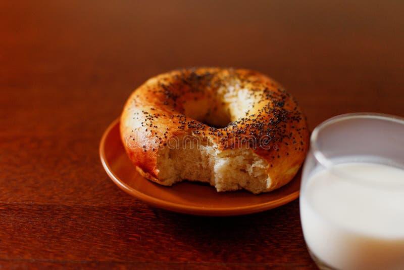 Een heerlijke ongezuurd broodje en een melk op een houten lijst stock afbeeldingen