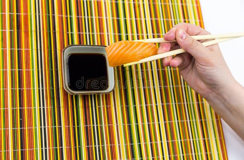 Een heerlijke sushirijst en een plak die van zalm, bamboestokken in zijn hand houden, worden verminderd in een kom met sojasaus o royalty-vrije stock fotografie