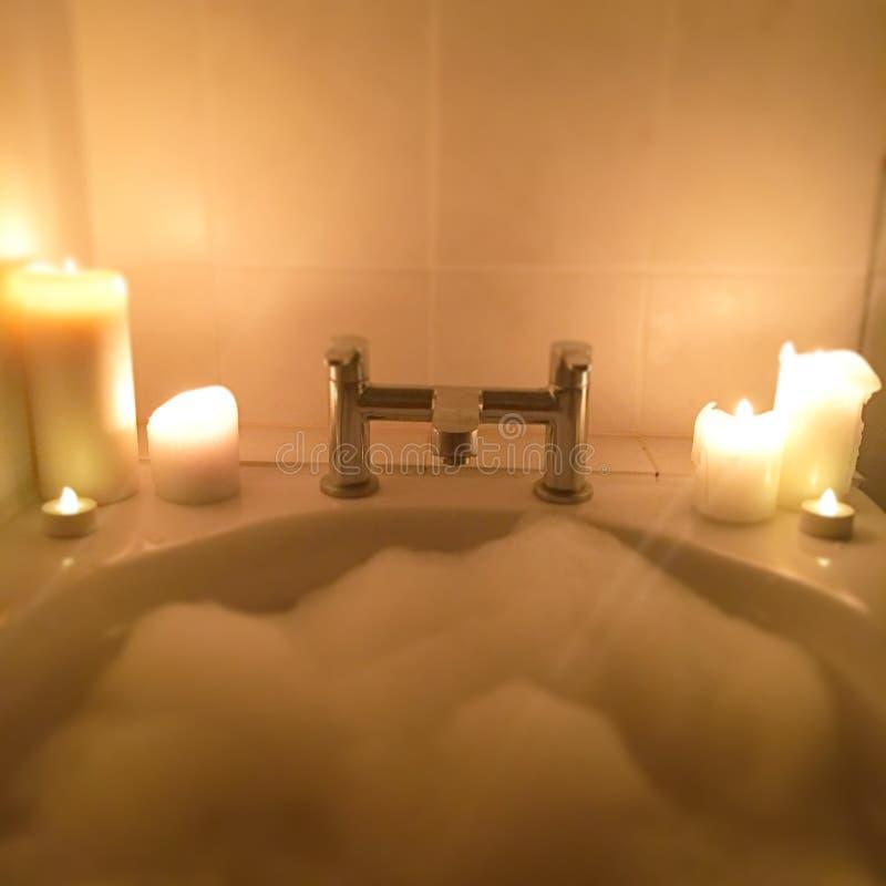 Een heet schuimbad en mooie kaarsen spreken voor zich stock foto's