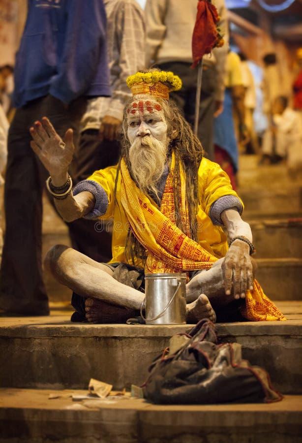Een heilige mens, een sadhuzitting op de dijk van Varanasi, tijdens een godsdienstige ceremonie stock fotografie