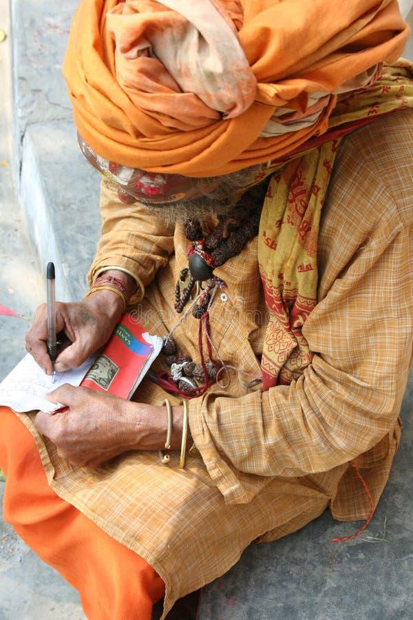 Een heilige Sadhu die op een document schrijft royalty-vrije stock fotografie