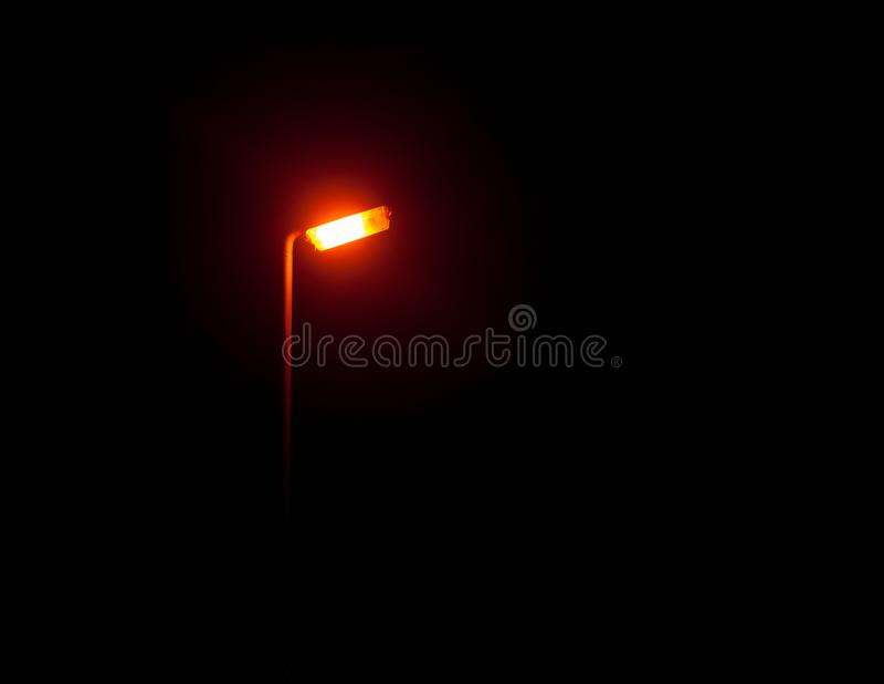 Een helder het gloeien straatlantaarnlicht in de donkere buitenkant bij nacht stock foto's