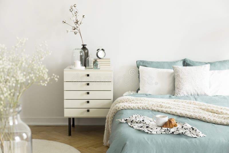 Een helder slaapkamerbinnenland met wijs groen en wit beddegoed, hoofdkussens op bed en een lade nightstand Echte foto royalty-vrije stock afbeeldingen