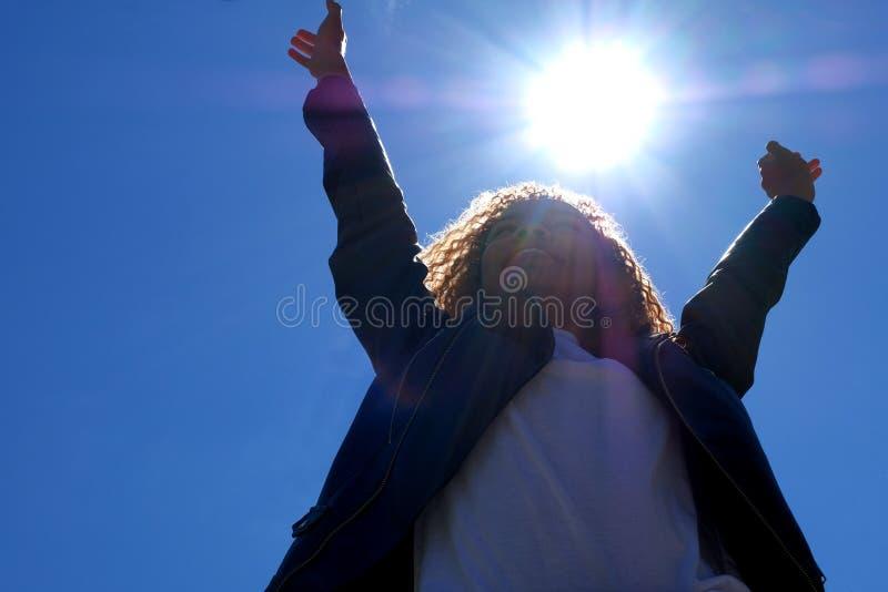 Een heldere middagzon in een blauwe hemel boven het hoofd van een mooi Afrikaans Amerikaans meisje in de straat Een gelukkige tie royalty-vrije stock fotografie