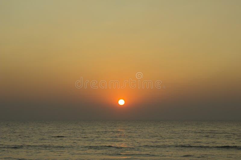 Een heldere zon over de horizon in een purpere roze grijze avondhemel tegen de achtergrond van de oceaan royalty-vrije stock foto's