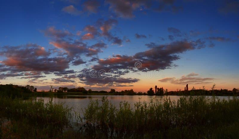 Een heldere zonsondergang in de nachthemel Het landschap met de rivier stock fotografie