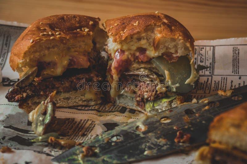 Een helft-gegeten hamburger op een lijst in een koffie stock foto's