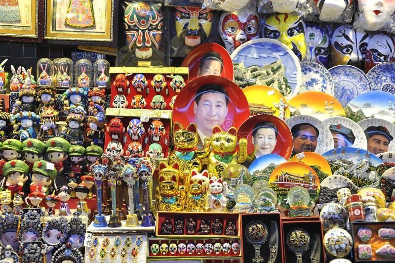 Een herinneringsbox bij een de nachtmarkt die van Peking Xi Jinping-gezichtsplaten en ander kitschvuilnis verkopen stock foto