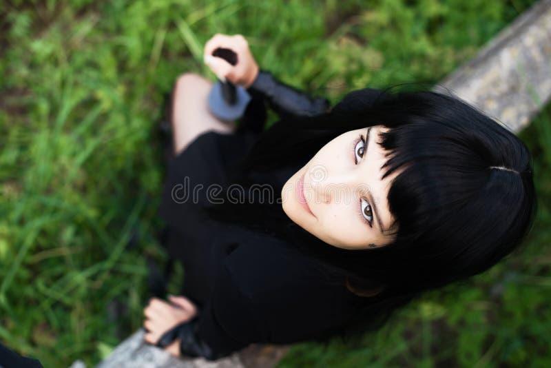 Een het branden brunette met een katana in zwarte kleren royalty-vrije stock fotografie