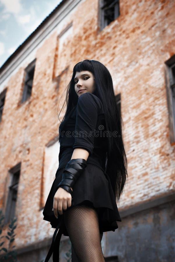 Een het branden brunette met een katana in zwarte kleren royalty-vrije stock afbeelding