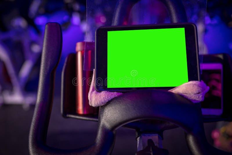 Een het cirkelen fiets met een groene het schermtablet op een handdoek in een donkerblauwe ruimte met LEIDENE verlichting stock foto's