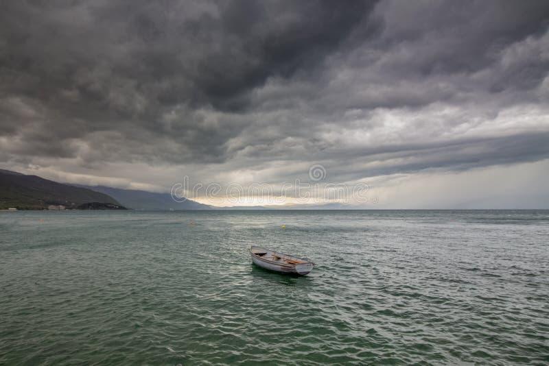 Een het donderen hemel boven Ohrid-Meer Landschap met boot stock foto's