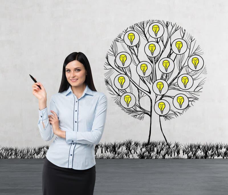Een het glimlachen mooi brunette wijst op iets door haar hand Een schets van een boom met gloeilampen wordt getrokken op concreet stock afbeelding