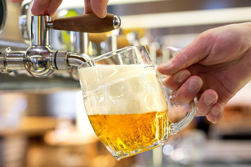 Een het lagerbierbier van het mensen gietend ontwerp in een ingedeukte glasmok in een moderne bar royalty-vrije stock foto