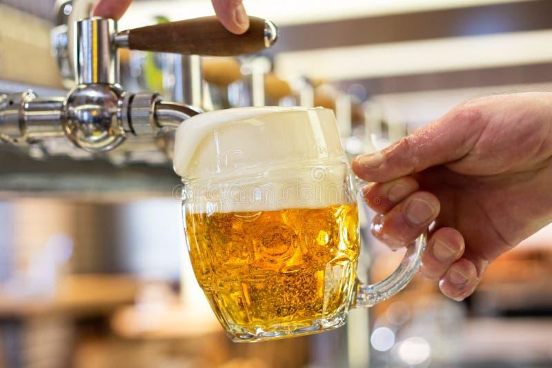 Een het lagerbierbier van het mensen gietend ontwerp in een ingedeukte glasmok in een moderne bar Overlopend glas royalty-vrije stock fotografie