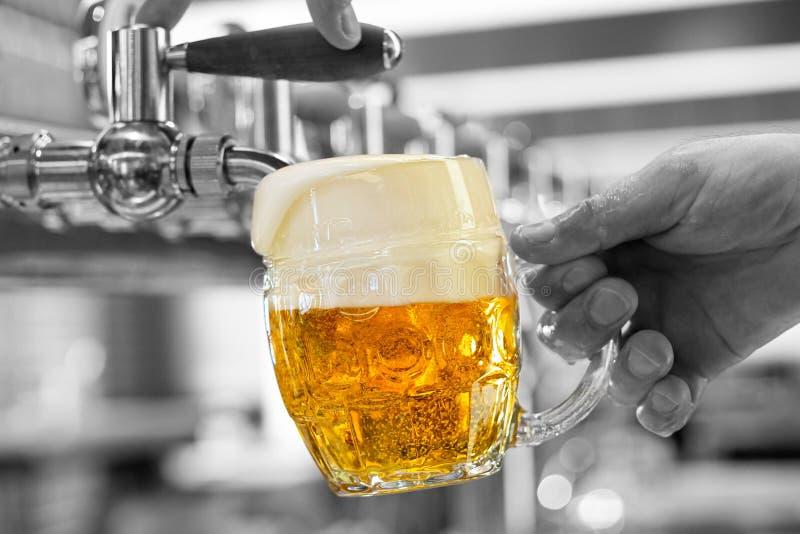 Een het lagerbierbier van het mensen gietend ontwerp in een ingedeukte glasmok in een moderne bar Overlopend glas Zwart-witte ach royalty-vrije stock afbeelding