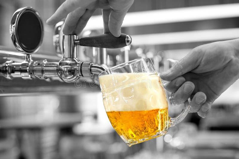 Een het lagerbierbier van het mensen gietend ontwerp in een ingedeukte glasmok in een moderne bar Zwart-witte achtergrond stock foto's