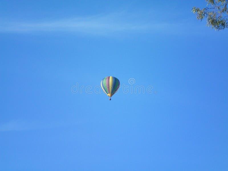 Een hete luchtballon tegen een blauwe hemel stock foto