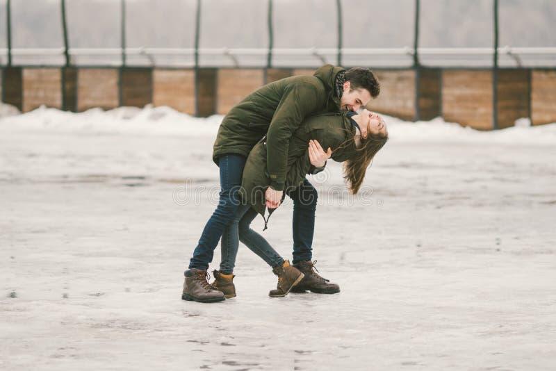 Een heteroseksuele paarjongeren in liefdestudenten een man en een Kaukasische vrouw In de winter, in het stadsvierkant met ijs wo stock afbeelding