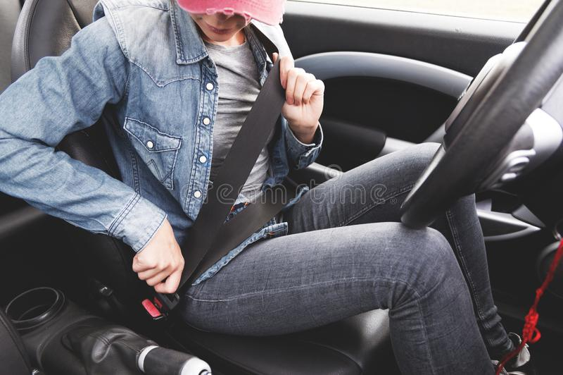 Een hipstermeisje die jeanskleren dragen maakt haar veiligheidsgordel in de auto vast royalty-vrije stock afbeeldingen