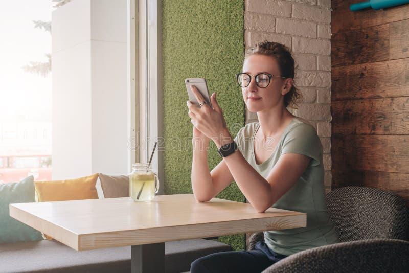 Een hipstermeisje in glazen zit in koffie bij lijst dichtbij venster, wacht op een orde en controleert e-mail op smartphone royalty-vrije stock fotografie