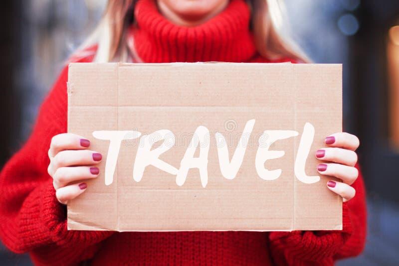 Een hipstermeisje in een rode sweater houdt een kartontablet met de inschrijvings 'reis stock afbeeldingen
