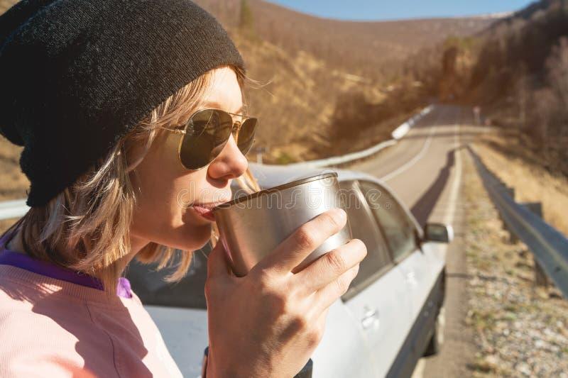 Een hipstermeisje in zonnebril en een zwarte hoed drinkt thee of koffie van een mok van een thermosfles in de aard in een reis royalty-vrije stock afbeelding