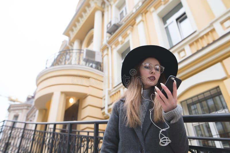 Een hipstersmeisje met een hoed en glazen bekijkt de telefoon op de achtergrond van een mooi huis stock afbeeldingen