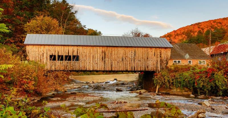 Een historische gele houten behandelde brug kruist een kleine stroom i stock afbeeldingen