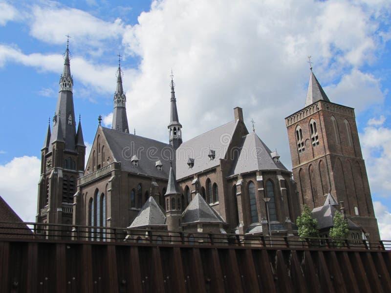 Een historische oude kerk en een toren in Cuijk, Nederland stock afbeeldingen