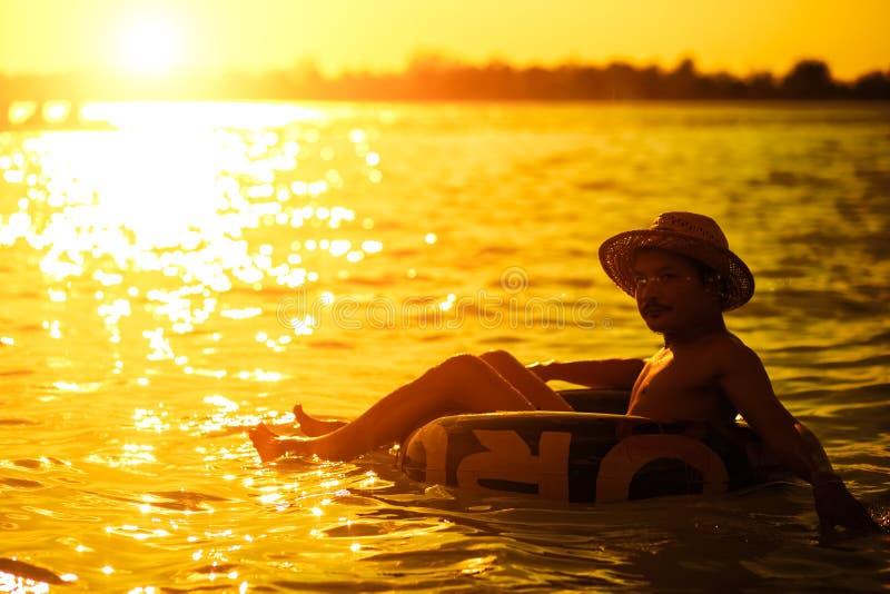 Een hoed van mensenwaren en hij is zwemt buis in het water stock afbeelding