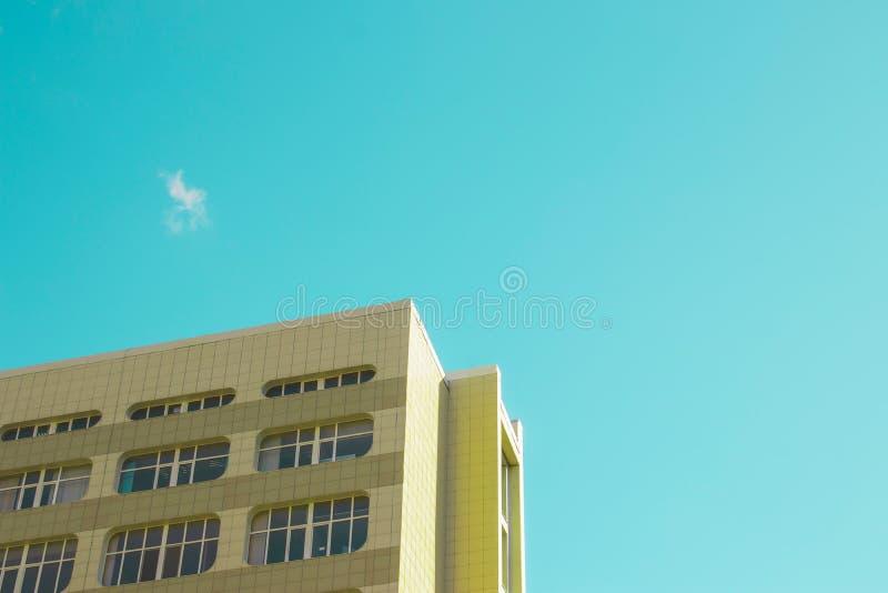 Een hoek van een gebouw met vele vensters tegen een blauwe hemel op een heldere zonnige dag royalty-vrije stock fotografie