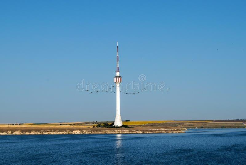 Een hoge toren op de kust Een mooie blauwe hemel en een zonnebloem ketenen in de afstand de vogels kruisen de hemel royalty-vrije stock afbeeldingen