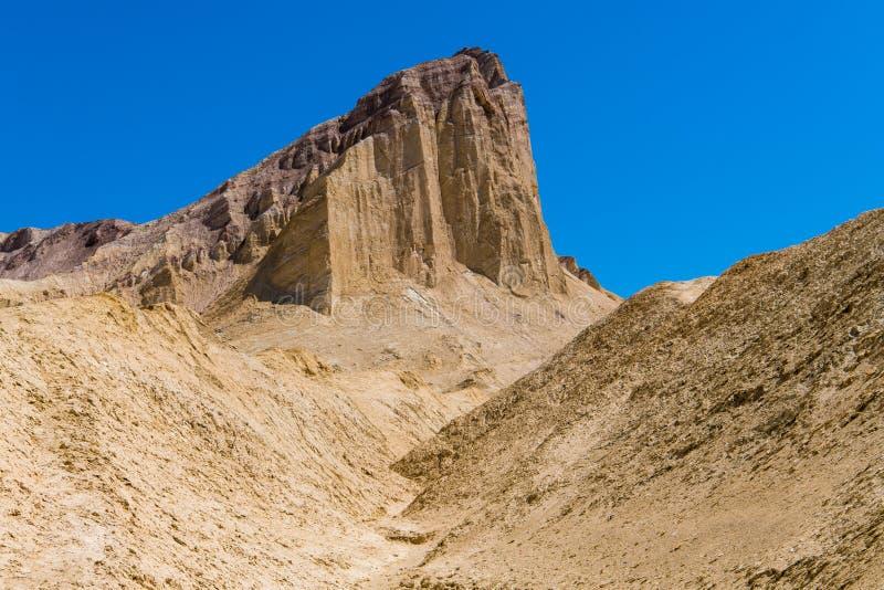 Een hoge woestijnpiek met zuivere klippen neemt boven een onvruchtbaar, gouden woestijnlandschap toe stock foto
