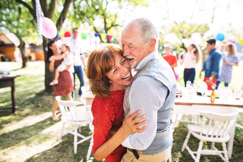 Een hoger paar die op een tuinpartij buiten dansen in de binnenplaats royalty-vrije stock afbeelding