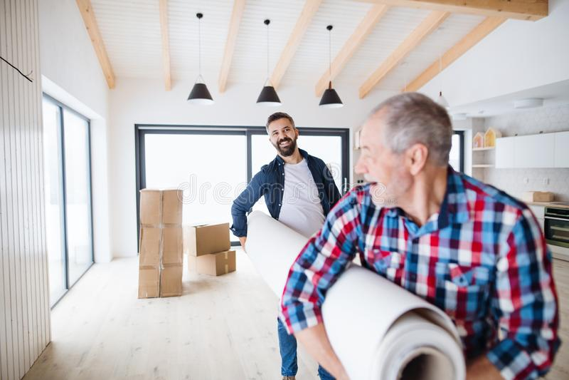 Een hogere mens die zijn zoon met het leveren van nieuw huis, een nieuw huisconcept helpen stock afbeelding