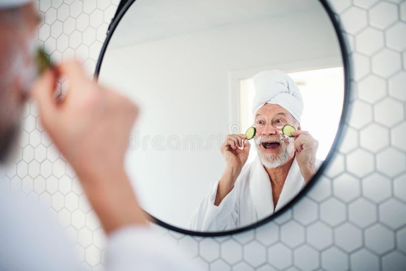 Een hogere mens met komkommer op ogen binnen thuis De ruimte van het exemplaar stock foto