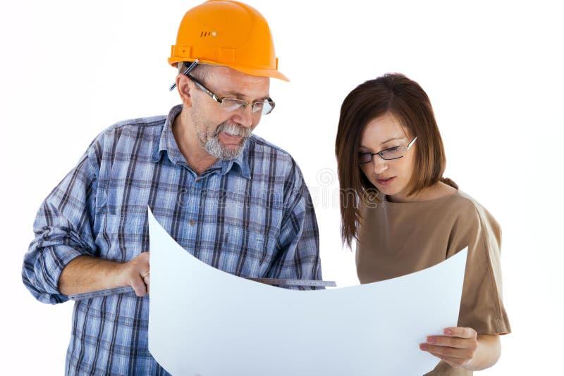 Een hogere mensenbouwer en een jonge ingenieur die het project bekijken stock afbeeldingen