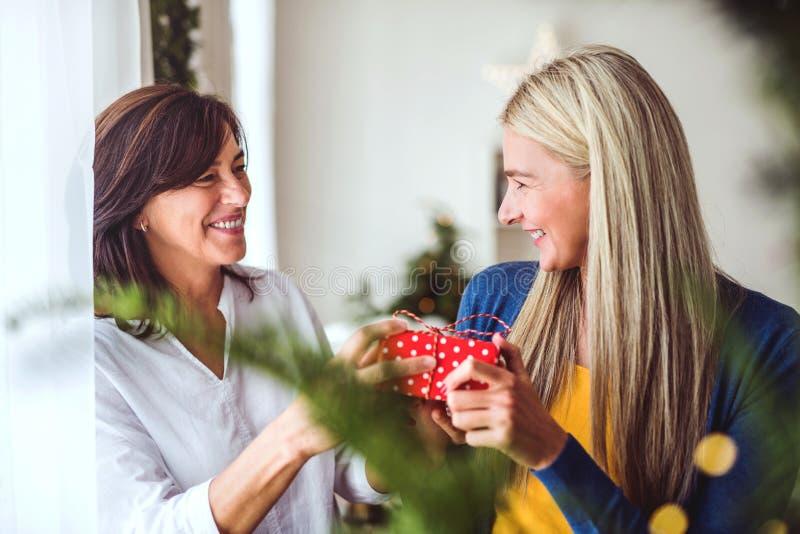 Een hogere vrouw die een heden geven aan een volwassen dochter thuis in Kerstmistijd royalty-vrije stock afbeeldingen