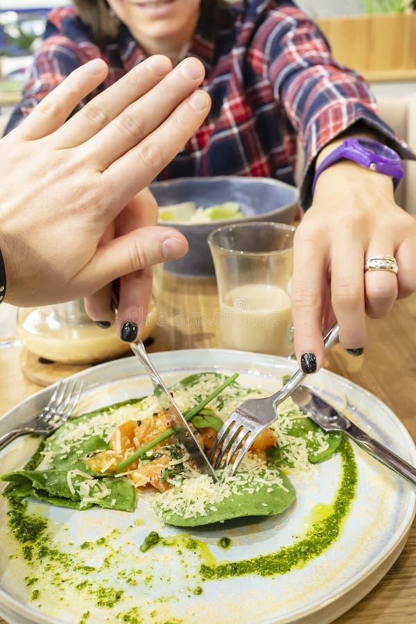 Een hongerig meisje in een plaidoverhemd met een mes en een vork probeert om een stuk van voedsel in de plaat van de zijn jonge m royalty-vrije stock foto