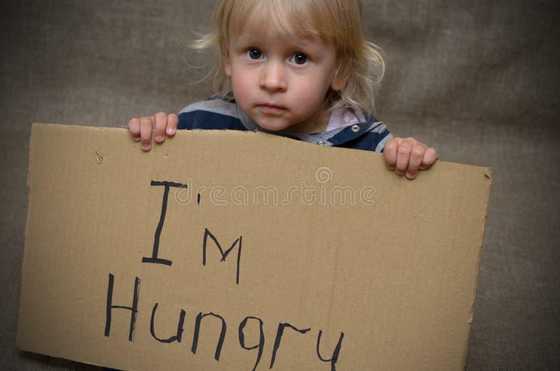 Een hongerige jongen en een meisje met een kartontablet met inschrijving I hongerige ` m Het sociale probleem royalty-vrije stock afbeelding