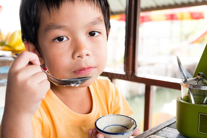 Een hongerige jongen zit bij de houten lijst voor eet dessert bij r royalty-vrije stock afbeeldingen